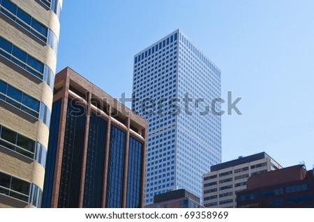 Tall buildings reach into a pale sky in Denver, Colorado.