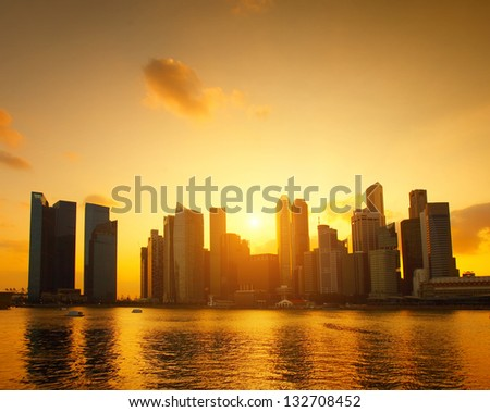 Tall buildings reflected in a water at sunset