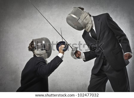 Tall businessman fencing with a smaller one