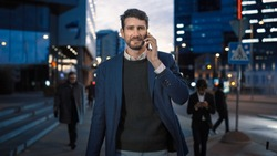 Tall Businessman in a Suit is Talking on a Phone While Walking in the City. He's Having a Pleasant Conversation. Office People Walk By. It's Evening with Atmospheric Urban Lights in the Background.