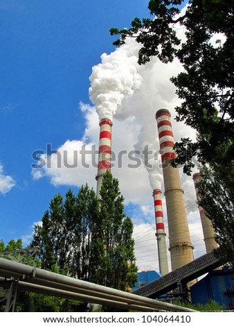tall chimneys flues of large amounts of steam against a blue sky
