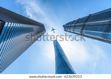 Shutterstock Tall city buildings and a plane flying overhead