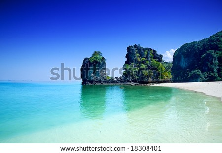 Tall cliffs with trees at Hong island surrounded by beautiful clear water of the Andaman sea.