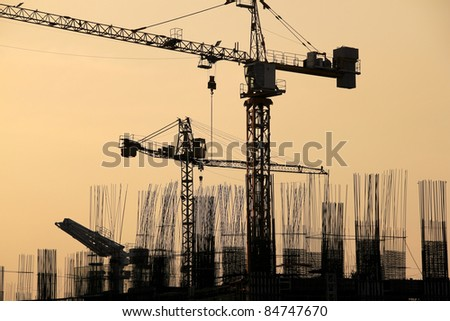 tall condominium buildings under construction in makati city manila in the philippines cranes and reinforcing rods silhouetted against the  sunset - stock photo