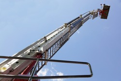 Tall extendable fire ladder close up in perspective on blue sky background, firefighter rescue equipment