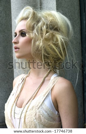 Tall fashion model in cream dress and big hair posing on a sunny day