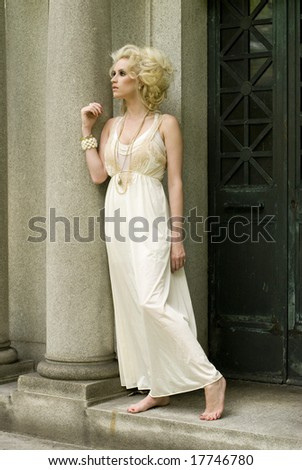 Tall female with white dress stands against a cement column with no shoes