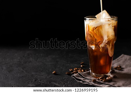 tall glass cold brew coffee with ice and milk on black or dark background #1226959195