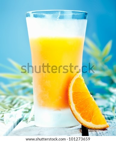 Tall glass of chilled orange cocktail with freshly squeezed juice against a blue summer sky