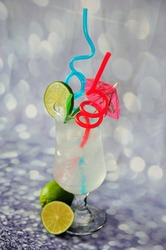 Tall glass of citrus juice with ice, lime slices, cocktail umbrella and straws on a gray shiny background. Close-up.