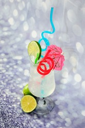 Tall glass of clear citrus juice with ice, decorated with a lime slice, cocktail umbrella and straws on a gray abstract background. Close-up.