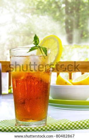 tall glass of cold iced tea with lemon and mint