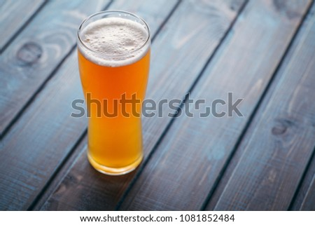 Tall glass of fresh pale ale on a blue wooden table at a pub