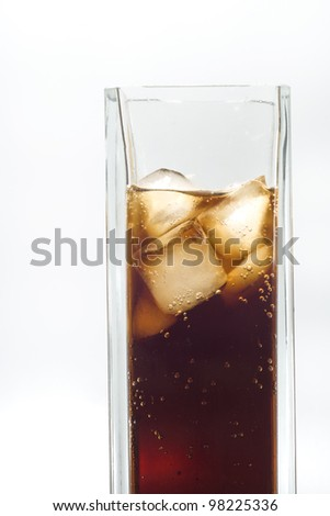 Tall glass of iced cola on white background