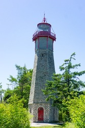 tall high stone lighthouse red door and top construction in park with grass trees on Toronto Island Ontario Canada