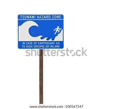 Tall isolated tsunami sign on a wooden post.