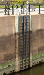 Tall ladder on the side of a concrete wall with water from the canal down below on a sunny day