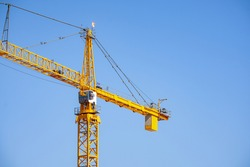 Tall, left facing, three quarter view of a large yellow tower crane up close.  Lots of blue sky and copy space.