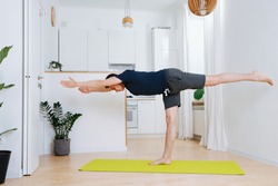 Tall man doing yoga on a mat in a kitchen at home during isolation. Standing on one leg with body and hands parallel to the floor.