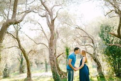 Tall man holds hands and kisses pregnant woman in a long dress against the backdrop of huge olive trees