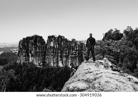 Tall man in black on cliff and watch to mountains. Dark silhouette of rocks. Black and white photo