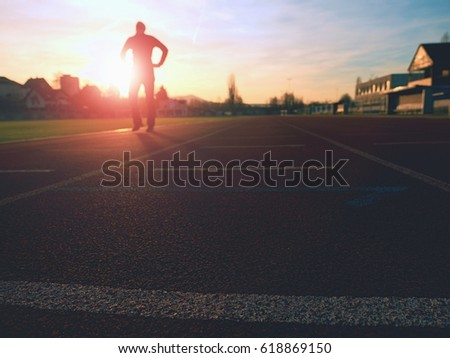 Tall man running on red running racetrack on the stadium. Sportsman in training clothes at amazing sunset. Sport and healthy lifestyle concept and jogging civic training workout #618869150