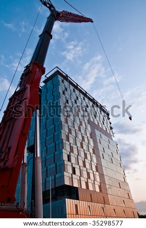 Tall massive crane and office building in construction