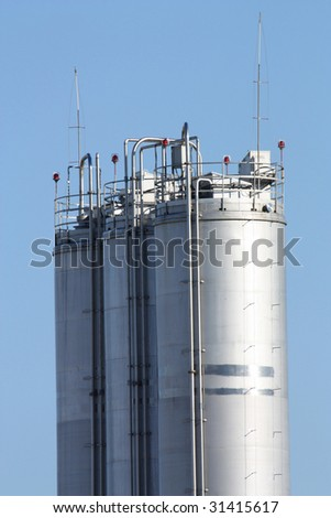 Tall metal silos for storing grain against a blue sky.