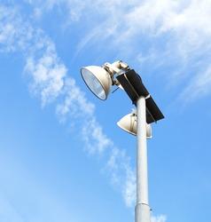 Tall modern floodlights against a bright blue sky