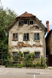 Tall narrow old abandoned suburban family house ruin with broken windows and cracked dilapidated facade surrounded with wire fence and trees
