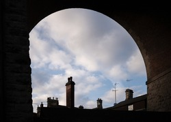 Tall old chimney pots tops under railway bridge arches on homes and houses below red brick train arch silhouetted on summer day in sunshine Mansfield town Nottinghamshire