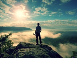 Tall photographer with baseball cap and tripod with camera in hands stand on rocky view point and watching down to deep misty valley bellow