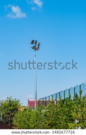 Tall pillar with spotlights to illuminate a football stadium against the sky with clouds  and protective mesh #1482677726
