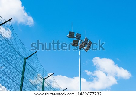 Tall pillar with spotlights to illuminate a football stadium against the sky with clouds  and protective mesh #1482677732