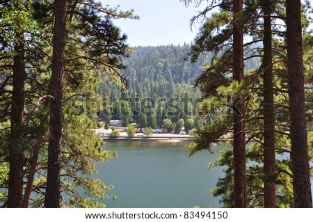 Tall pine trees frame this view of Lake Gregory in the Southern California mountains.