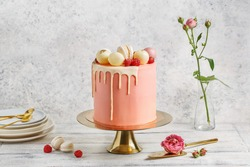 Tall pink cake decorated with macaroons, raspberries and chocolate balls on golden cake stand over white background with flowers and berries. Side view, copy space