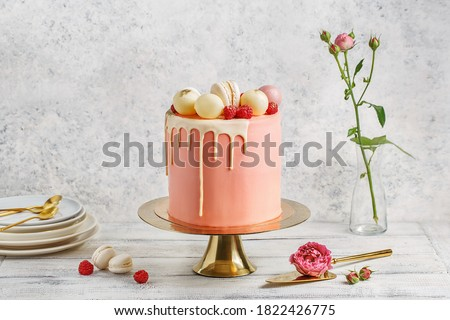 Tall pink cake decorated with macaroons, raspberries and chocolate balls on golden cake stand over white background with flowers and berries. Side view, copy space Foto stock ©