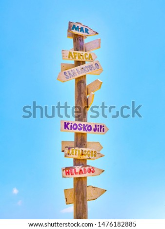 Tall post with colored wooden signboards pointing to various destinations and a beach services in Spanish on a blue sky. Sea, Africa, San Bartolo, Hippy Kiosk , drinks and Ice Creams.