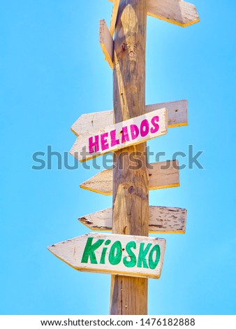 Tall post with colored wooden signboards pointing to various destinations and a beach services in Spanish on a blue sky. Kiosk and Ice Creams.