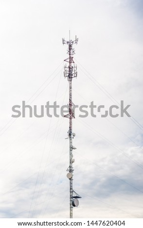 Cell phone antennas on a red and white tower Images and Stock Photos