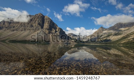 Tall rocky mountain peak jutting out of the ground surrounded by low hanging misty clouds reflected in a crystal clear lake on a still morning in the canadian Rockies #1459248767