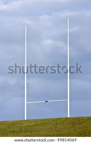 Tall rugby union goal posts and cloudy blue skies