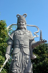 Tall sculpture with sword monument holding miniature temple pagoda in asia