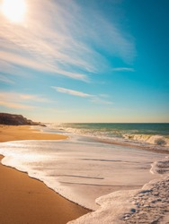 Tall seascape with white circular waves rolling in on clean beach sand
