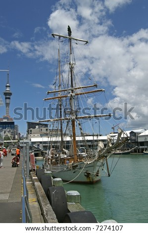 Tall ship decorated with Christmas tree on top of the mast anchoring in Auckland harbor, New Zealand