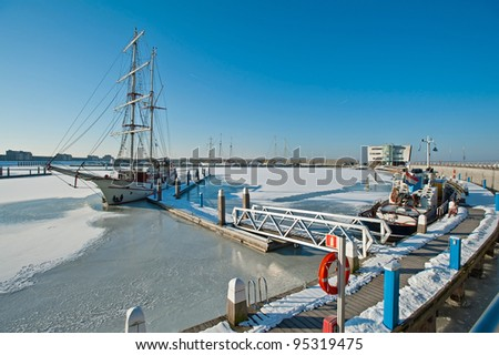 Tall ship in a frozen harbor in winter #95319475