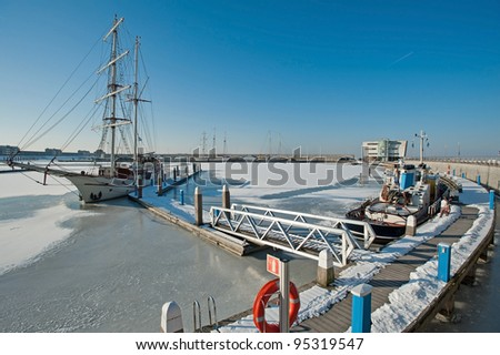 Tall ship in a frozen harbor in winter #95319547
