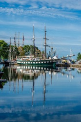 Tall Ships and their refelction on a harbor on a summer day with a lightly clouded blue sky.