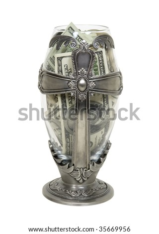 Tall silver cross vessel representing religion filled with large amounts of cash - path included