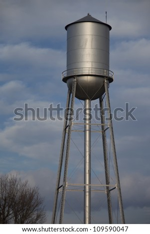 Tall silver water tower with cloudy blue sky background #109590047